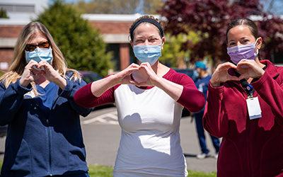 Bilden visar tre kvinnor med munskydd som formar hjärtan med händerna